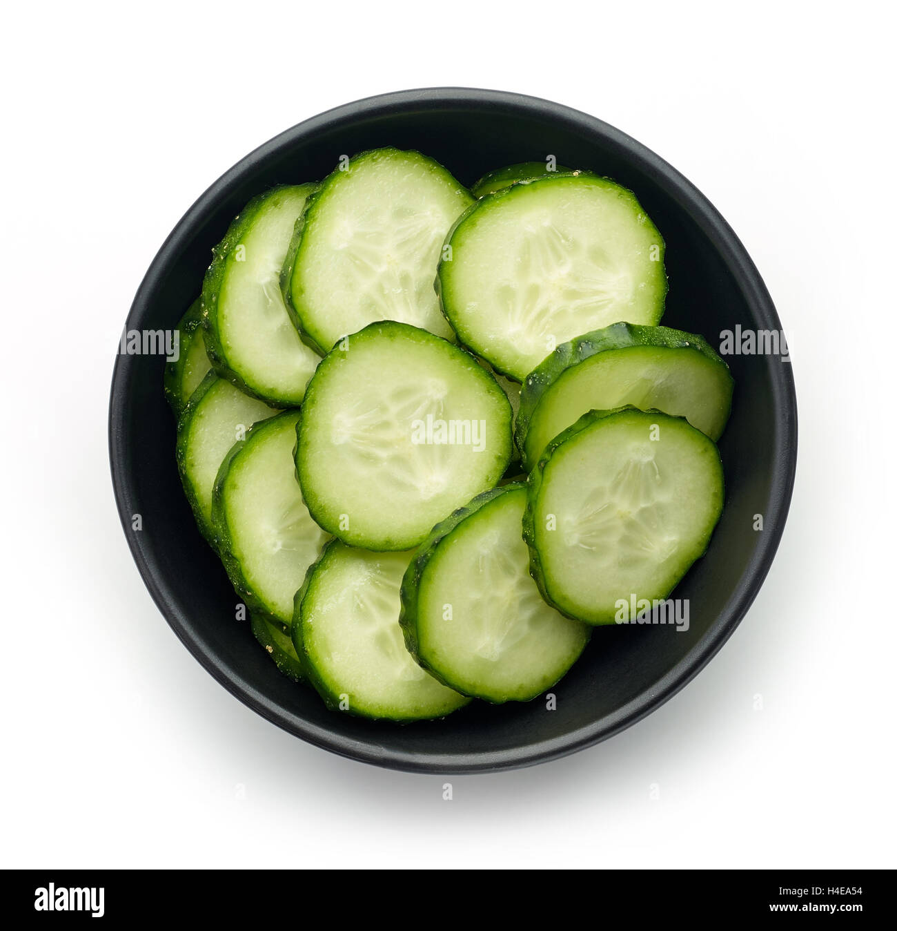 Black bowl of fresh cucumber slices isolated on white background, top view - Stock Image