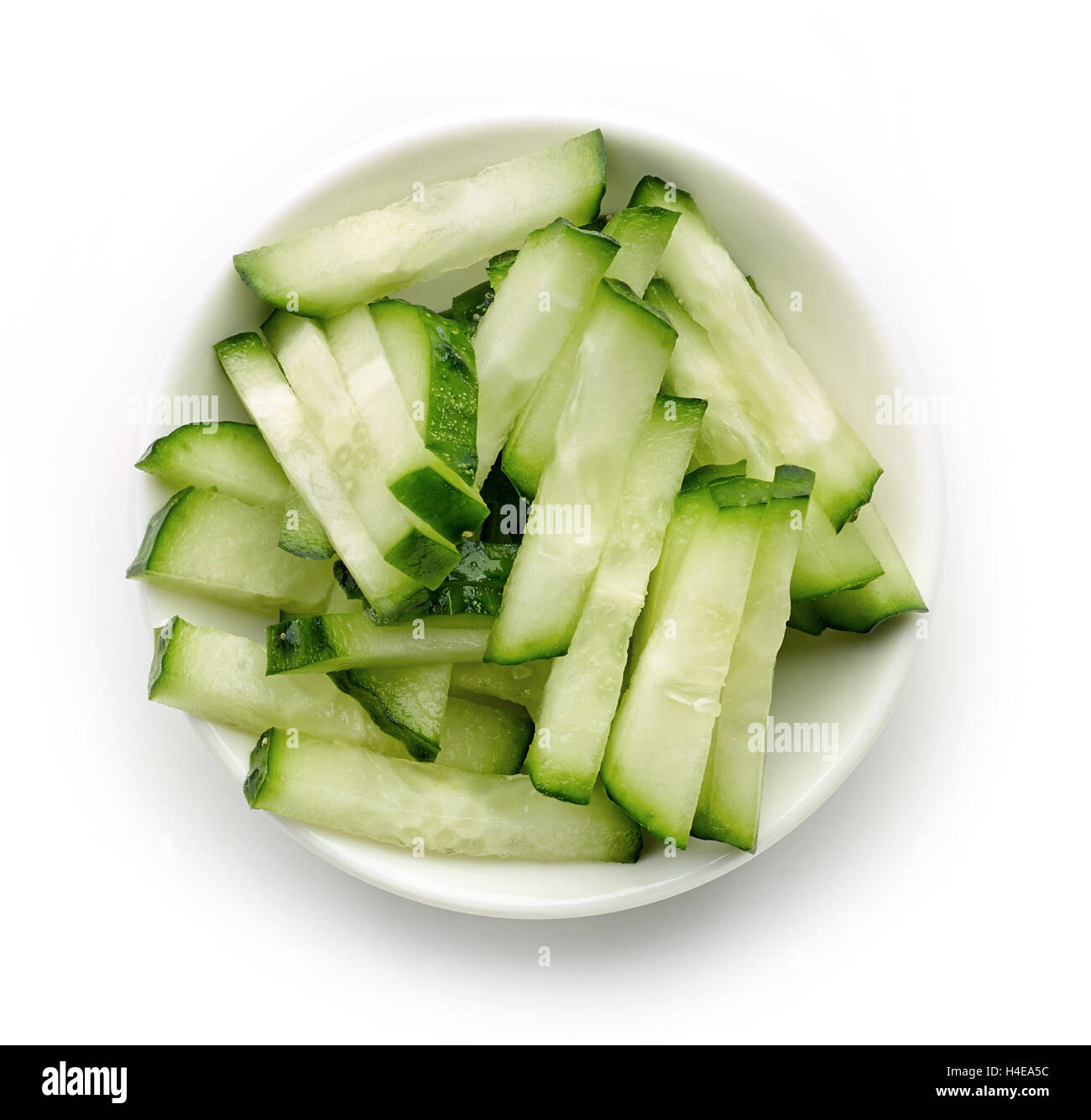 Bowl of fresh cucumber slices isolated on white background, top view - Stock Image