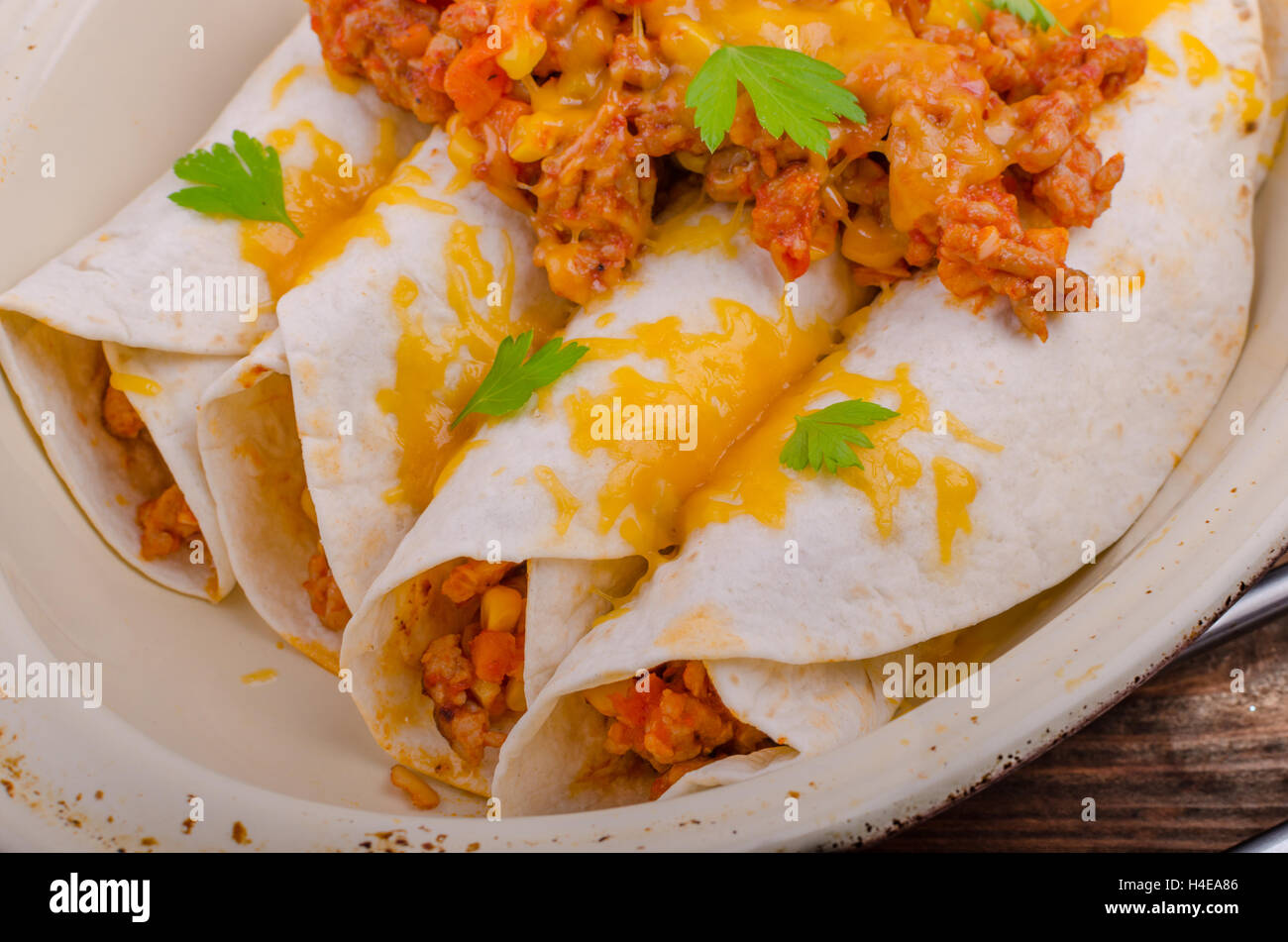 Baked meat tortilla with cheddar cheese, chilli peppers and corn, lime drink Stock Photo