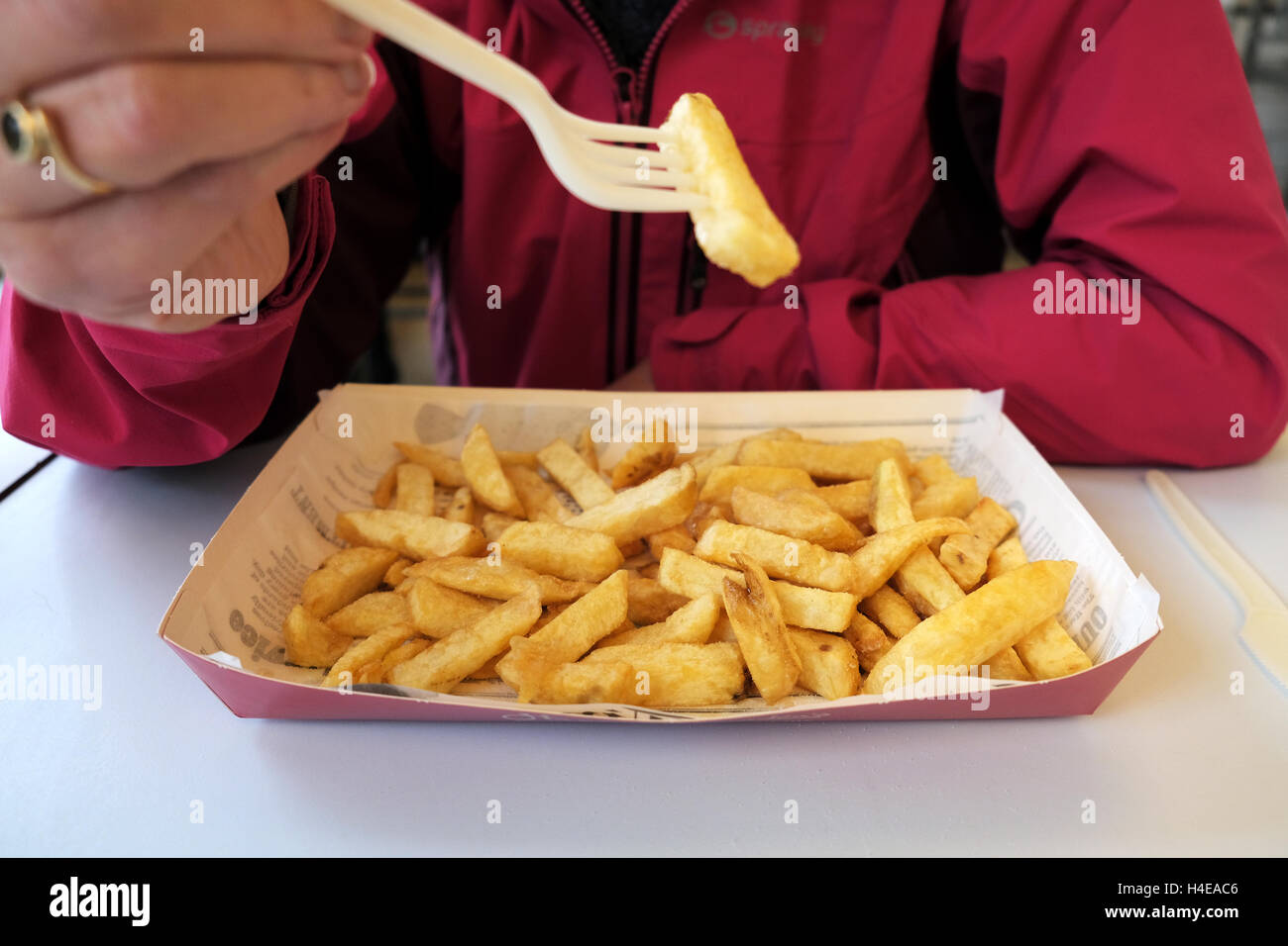 A lady eating a portion of freshly cooked fish and chips from a Harry Ramsden fish and chip shop Stock Photo