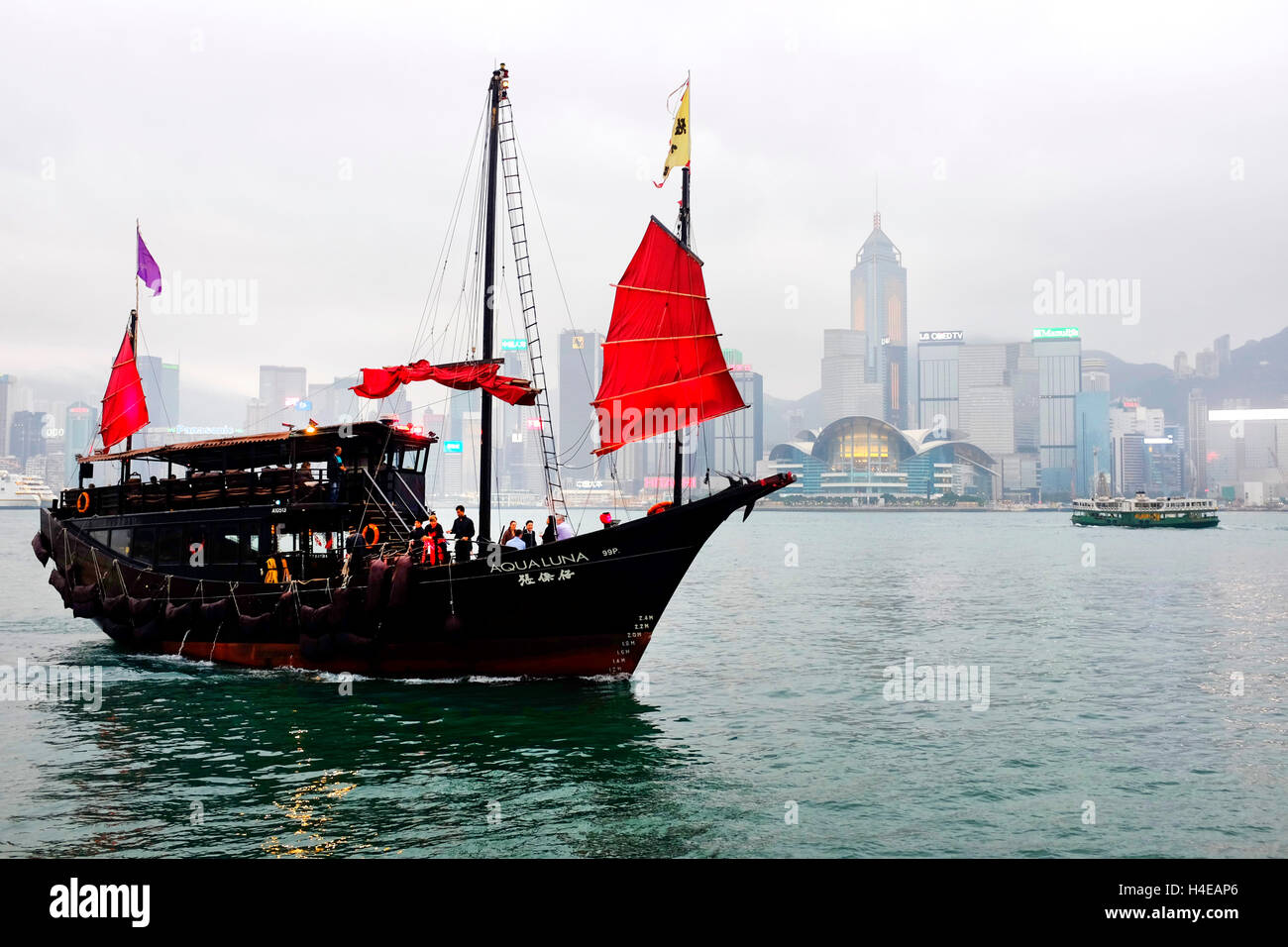 Red sail junk boat in the Victoria Harbour, Hong Kong - Stock Image