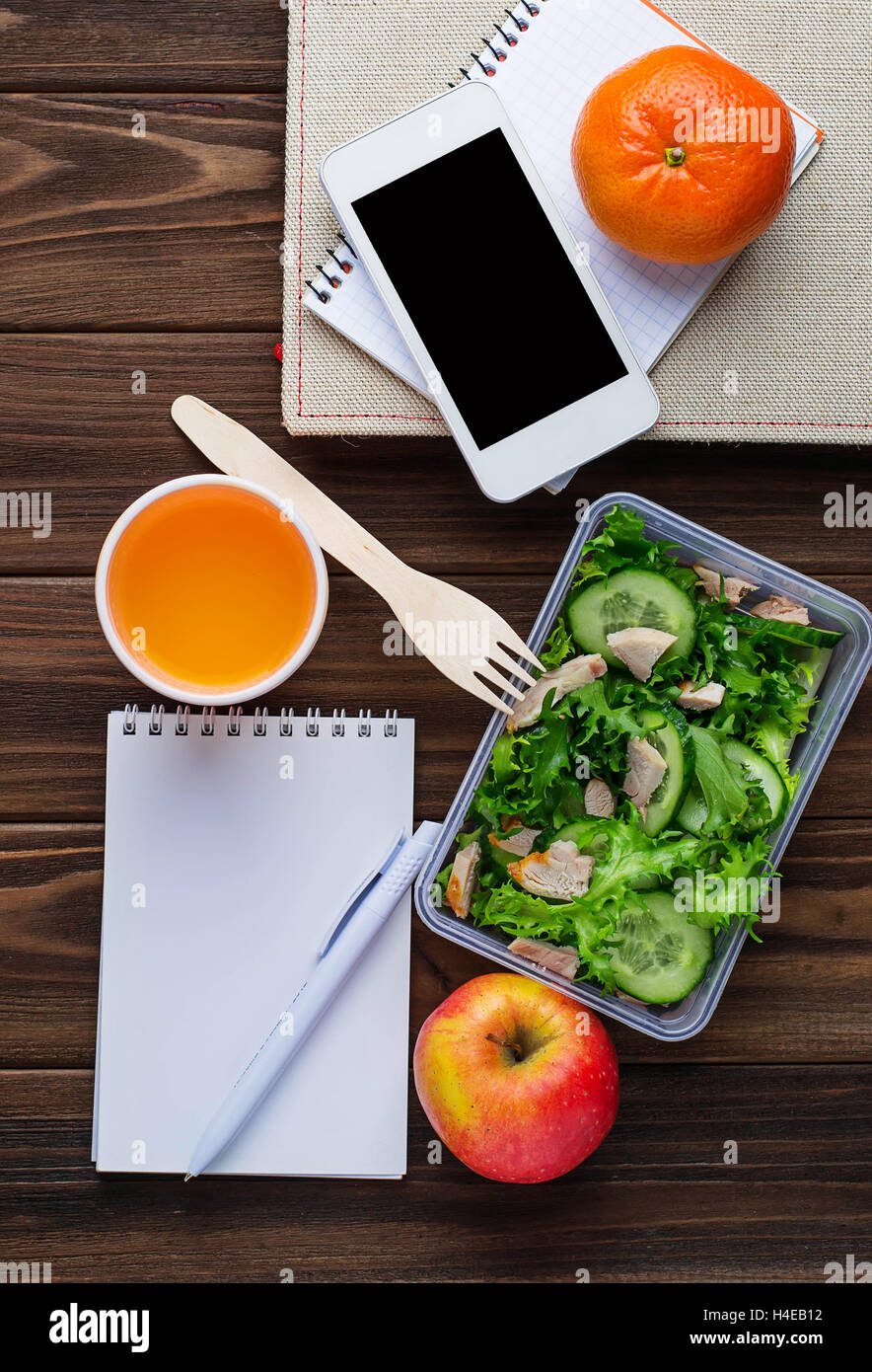 Lunch box with salad, notebook and phone. Selective focus, space for text - Stock Image