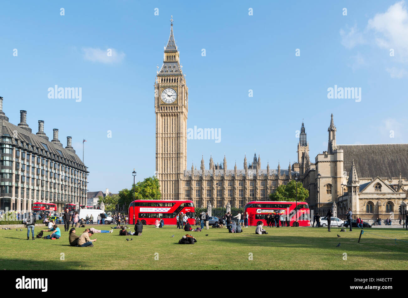 View across Parliament Square Garden towards Big Ben and the Palace of Westminster / Houses of Parliament with red - Stock Image