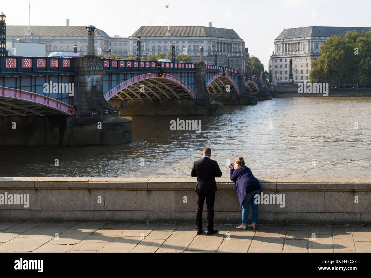 Man and woman taking photographs of the River Thames and Lambeth Bridge, London - Stock Image