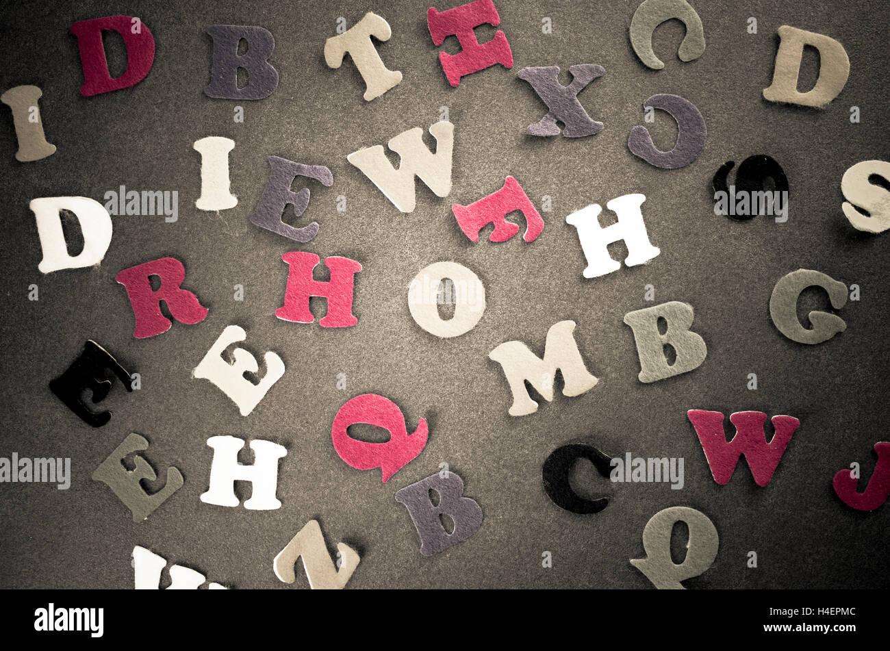 random felt cut alphabet letters on a dark slate worktop - Stock Image