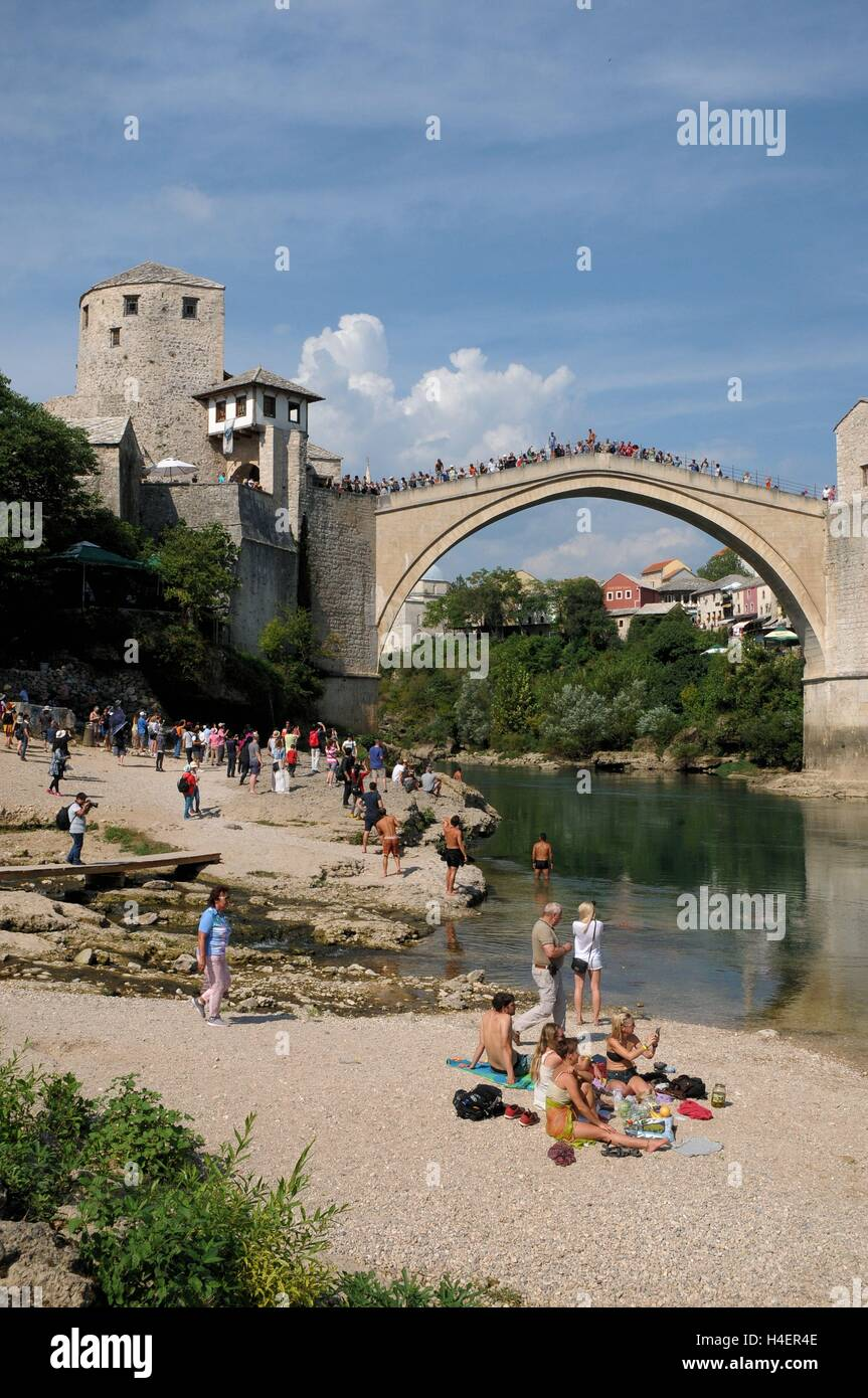 Tourists relaxing by the Stari Most, Mostar, Bosnia Herzegovina - Stock Image