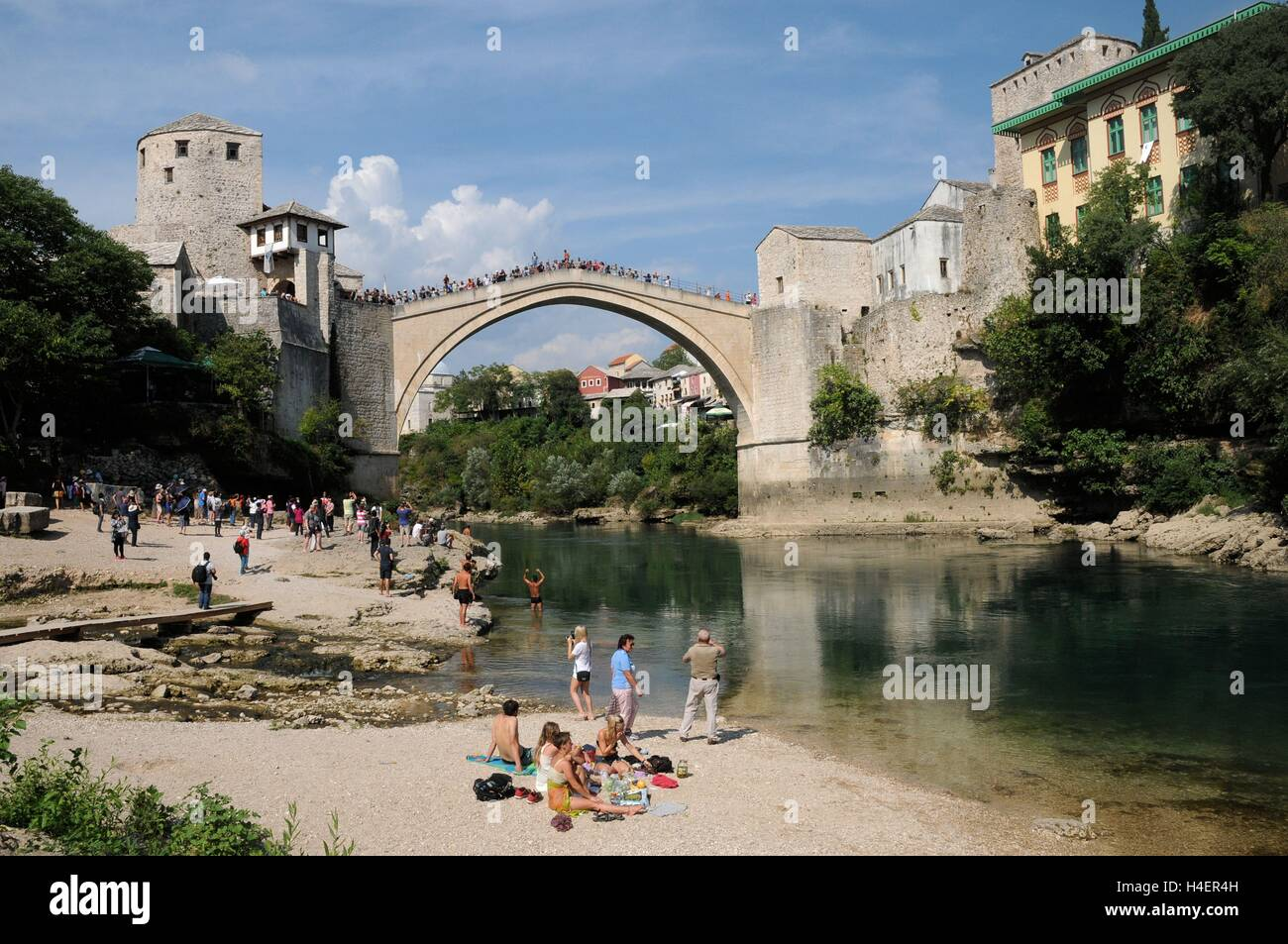 Relaxing by the riverside in front of the Stari Most bridge, Bosnia Herzegovina. - Stock Image