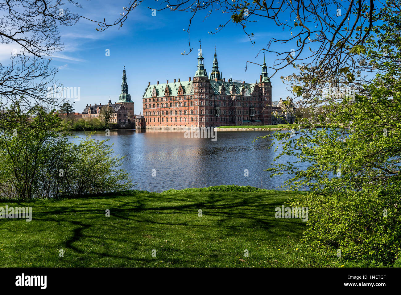 Morning sight of Frederiksborg Castle across the lake, settled in a town Hilerod, north-west of Copenhagen, Denmark - Stock Image