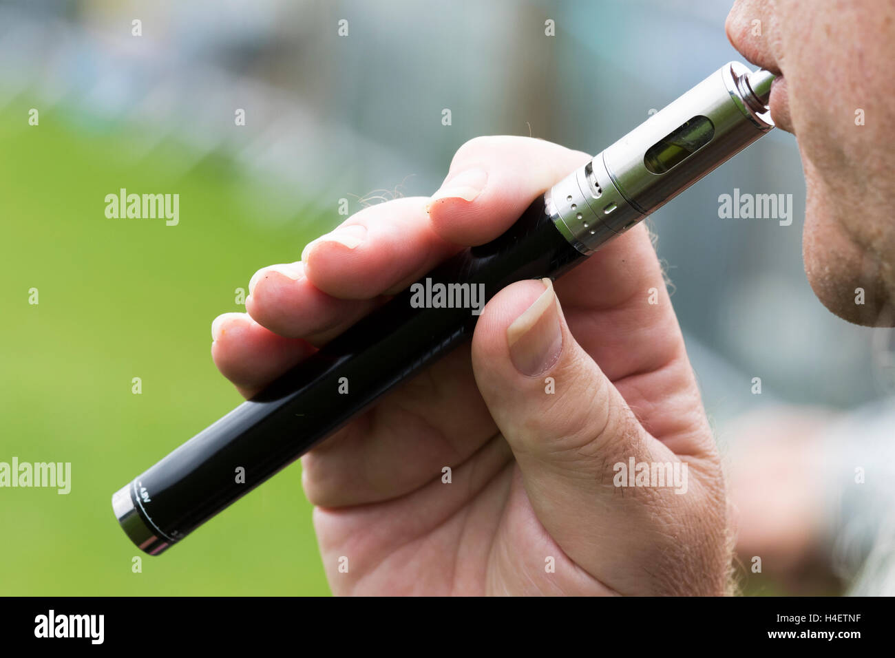 Man using an e-cigarette. - Stock Image