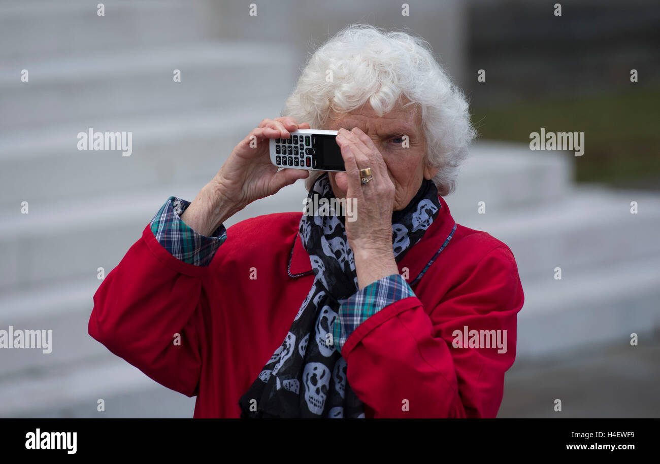 An elderly pensioner oap using technology mobile phone to take a picture. - Stock Image