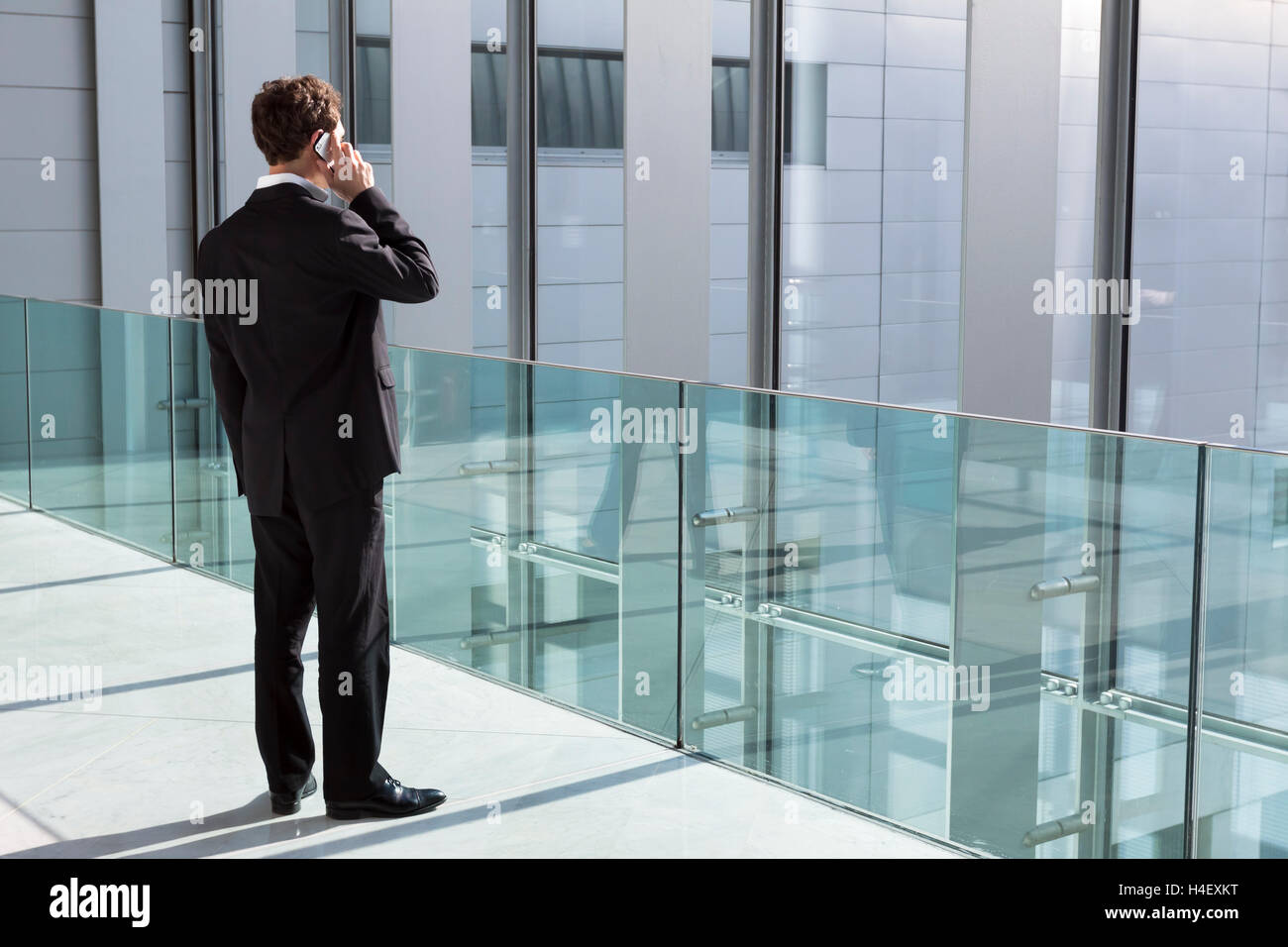 Businessman phoning with new technology smartphone in modern office building - Stock Image