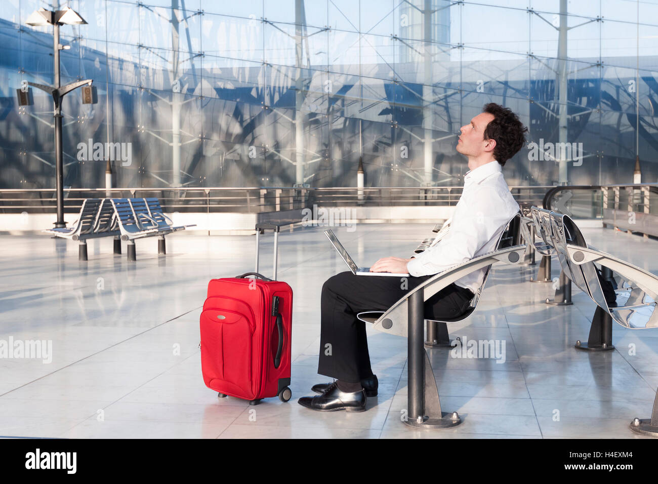 Businessman imagining ideas while waiting in airport lounge - Stock Image