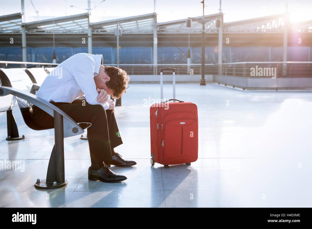 Depressed traveler waiting at airport after flights delays and cancellations - Stock Image