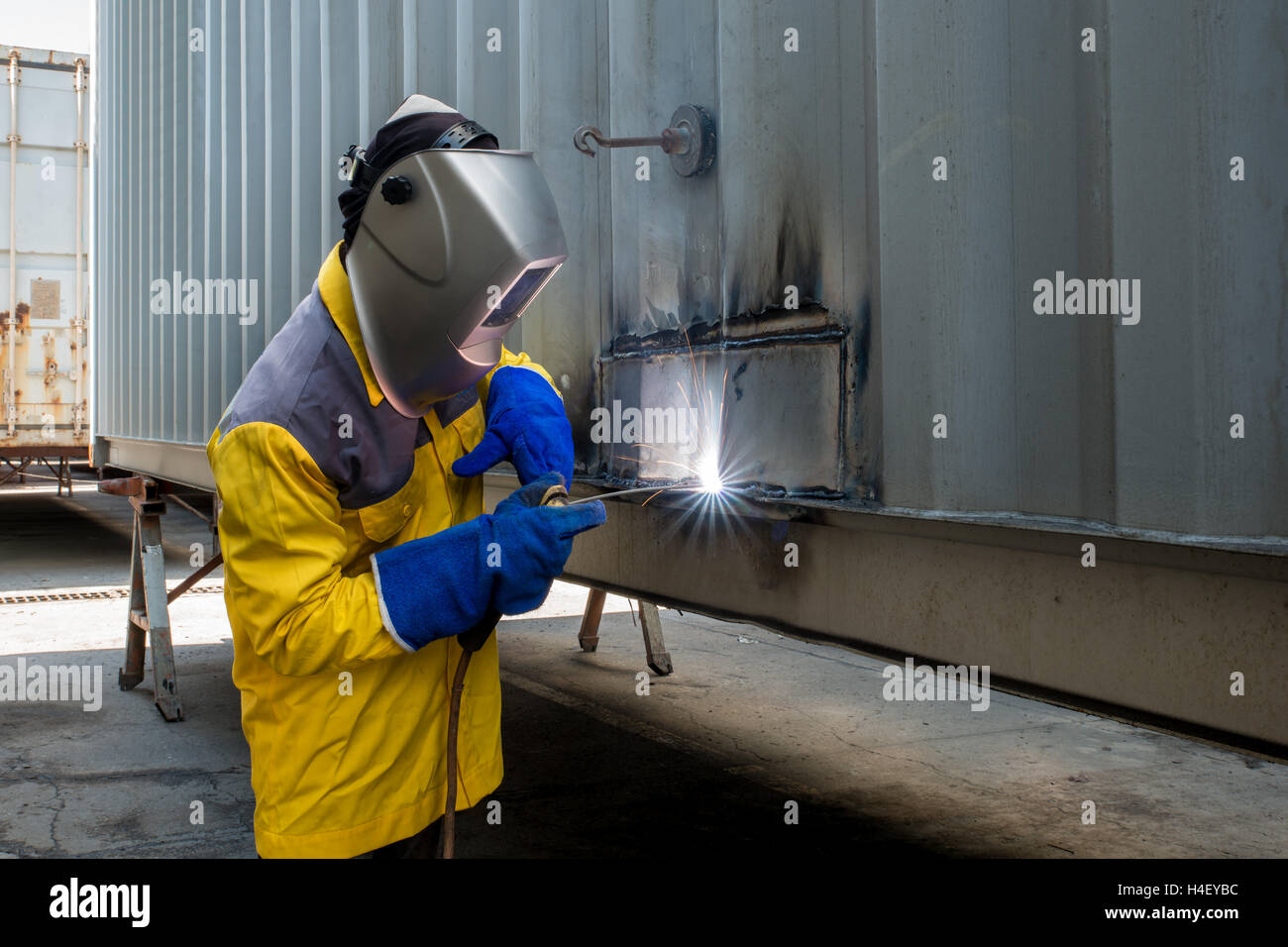Industry worker with welding steel to repair container structures manufacture workshop in industry factory. Stock Photo