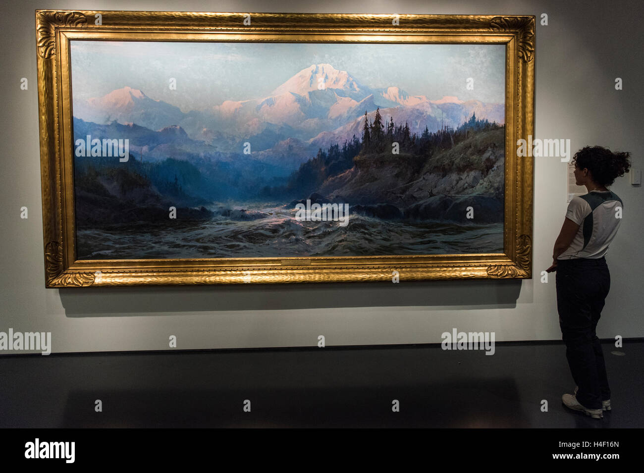 Tourist looking at painting of Denali mountains by Alaska painter Sydney Laurence, Alaska Native Heritage Centre, - Stock Image