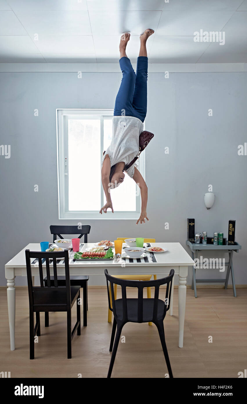 Thai woman having a fun time at the Upside-Down illusion house in Pattaya Thailand S. E. Asia - Stock Image