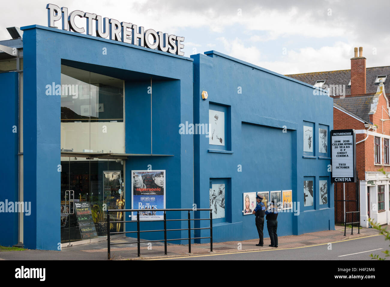 Exeter, Devon, England, UK - 30 September 2016: Unidentified policemen look at what films are on at Exeter Picturehouse. - Stock Image