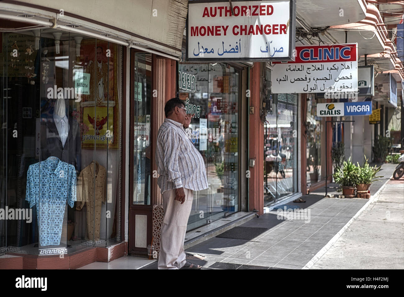 Portly Arab businessman outside chain of shops with a girth seemingly indicative of prosperous times. - Stock Image