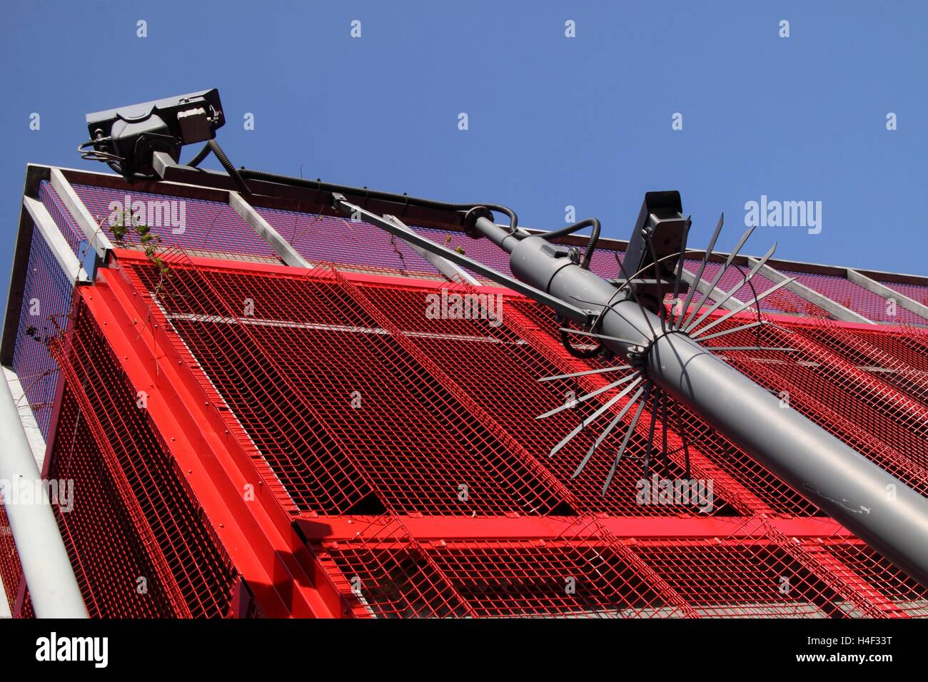 CCTV cameras outside the bright red car park railings of Brunel Street car park in Birmingham city centre - Stock Image