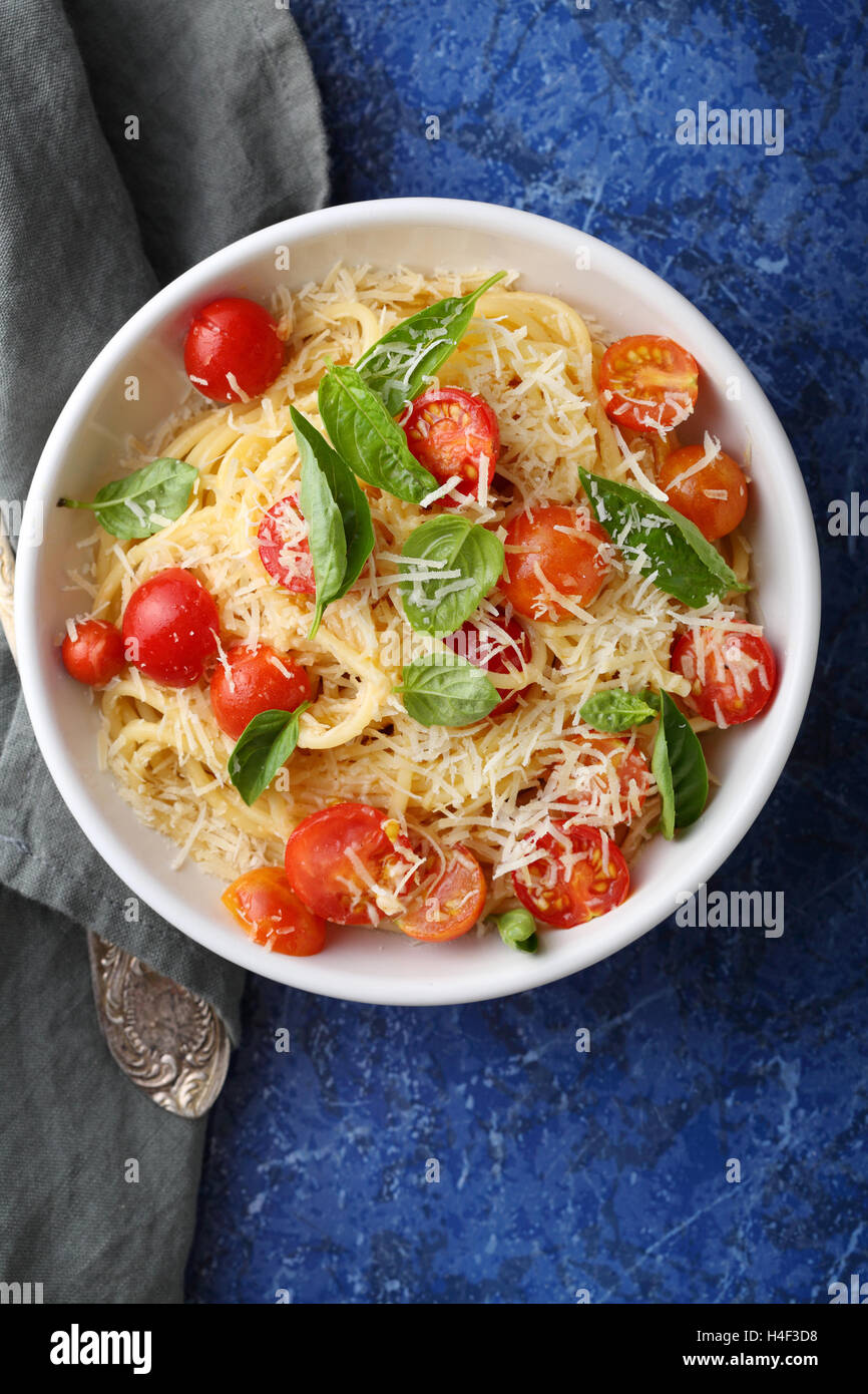 Spaghetti with tomatoes and cheese, food top view - Stock Image
