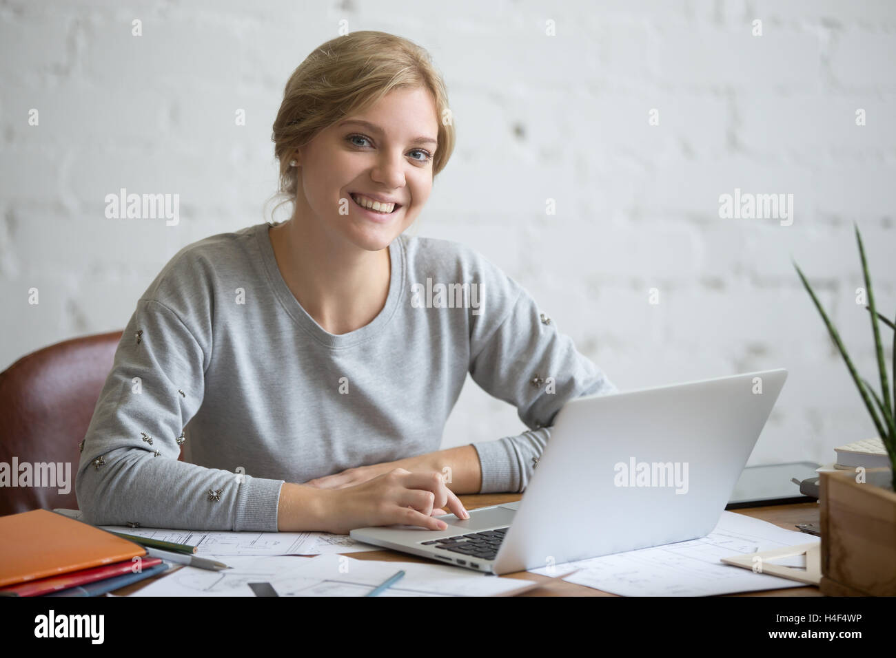 Portrait of a smiling student girl at desk with laptop - Stock Image