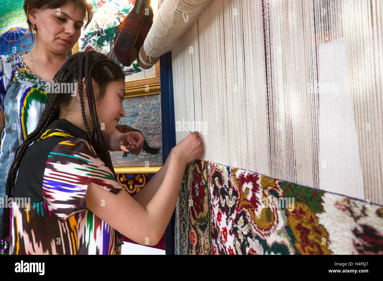 Women show for public traditional knotting a handmade carpet in central park during Nowruz holiday in Khujand city, - Stock Image