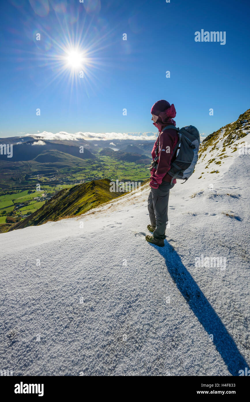 Female hillwalker on Blencathra (Saddleback) in winter looking down Hall's Fell Ridge to St John's in the - Stock Image