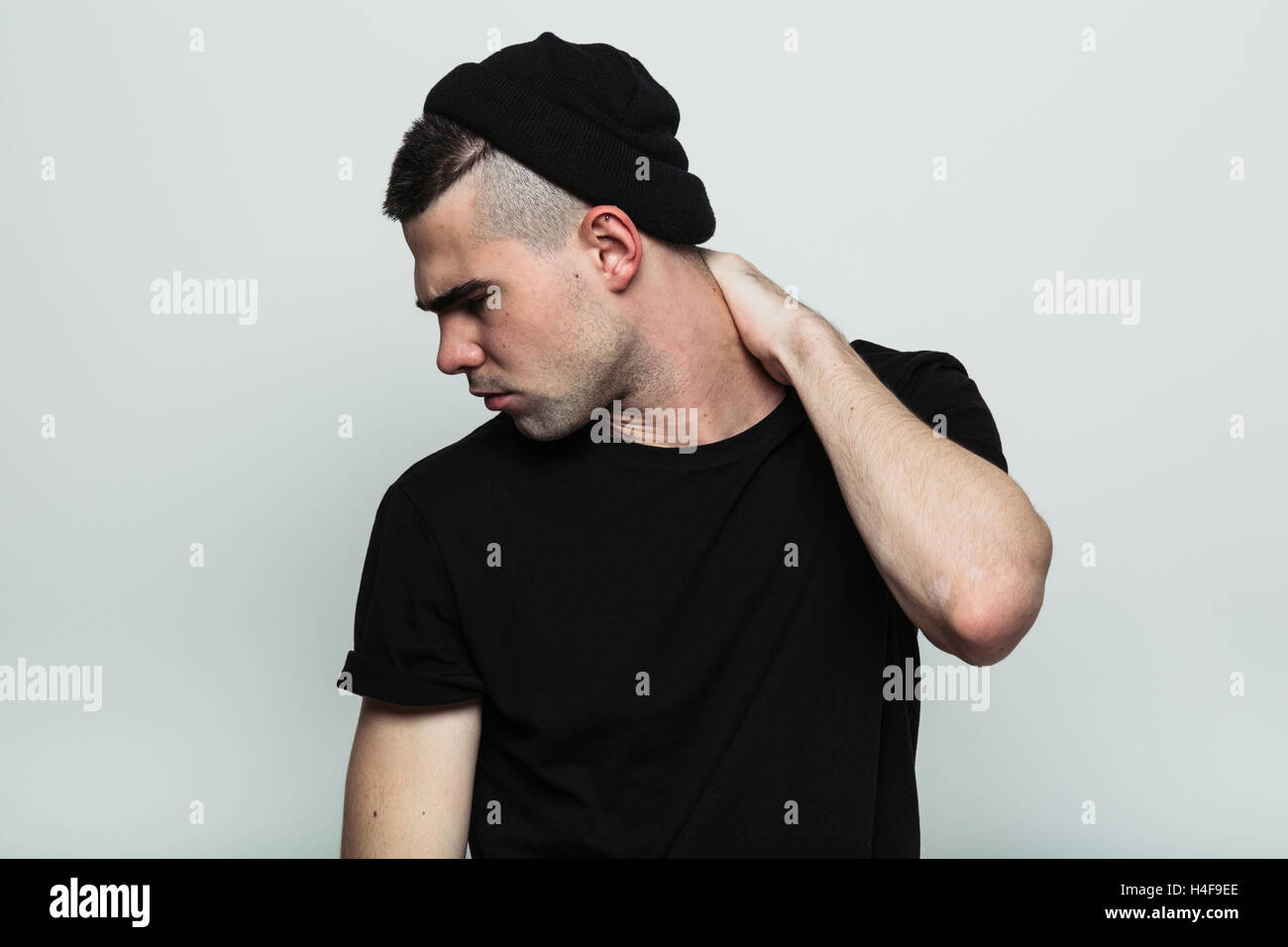Portrait of man turned away with hand on neck Stock Photo