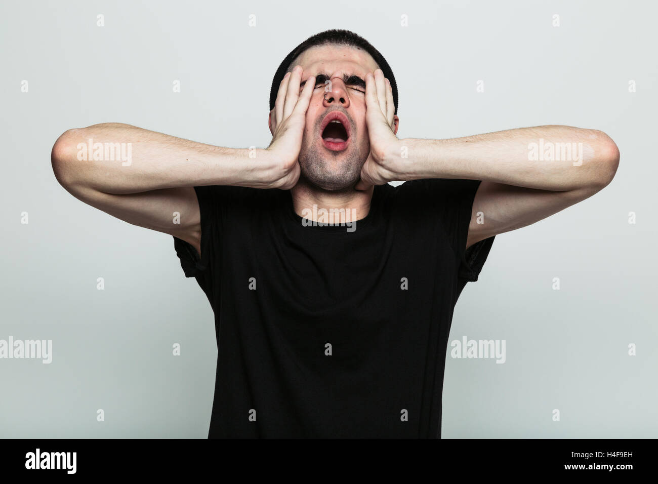 Annoyed male in a black t-shirt - Stock Image