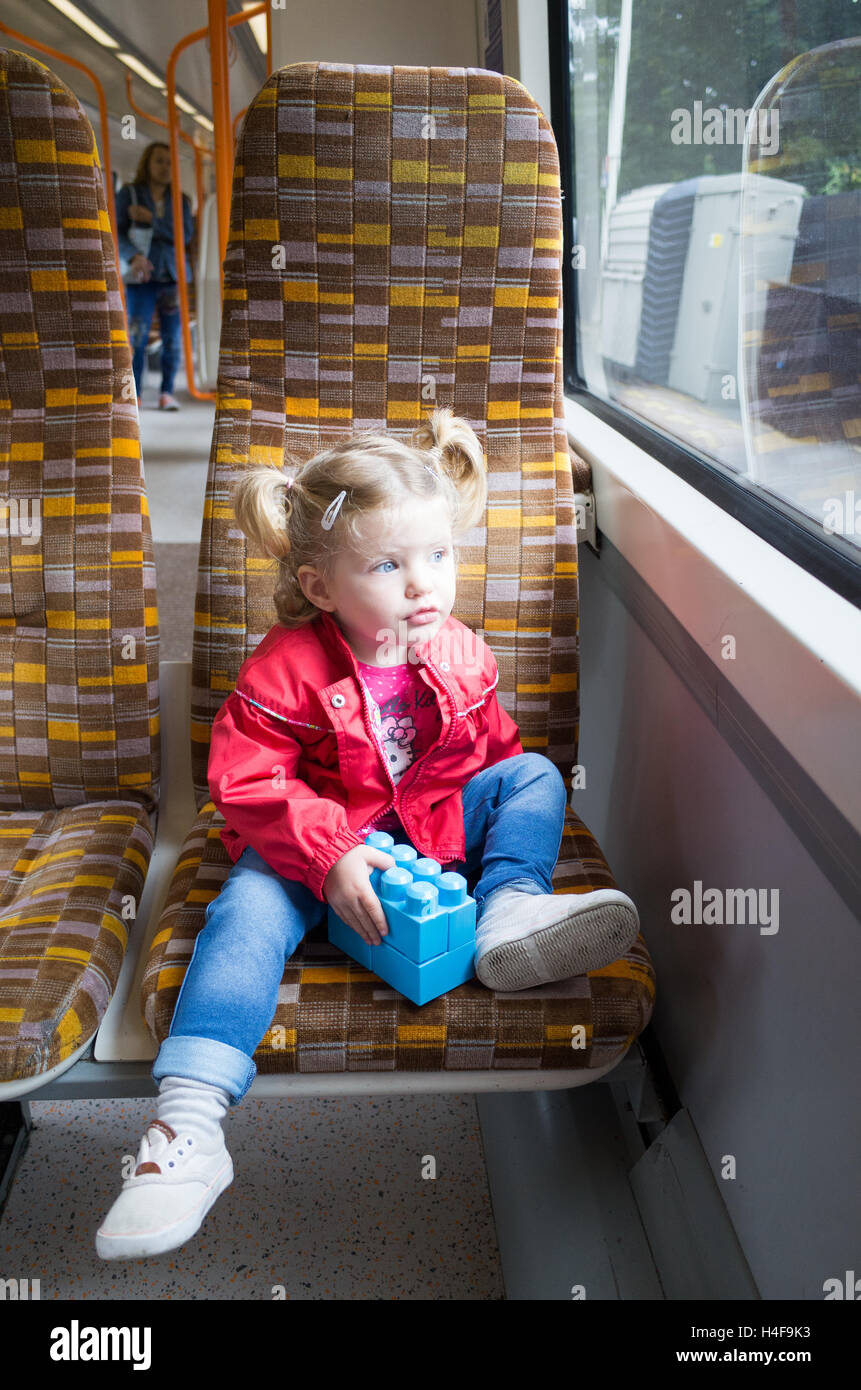 Two year old toddler travelling on the London Overground, UK - Stock Image