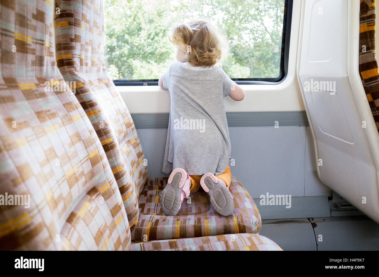 Two year old toddler travelling on the London Overground, England, UK - Stock Image