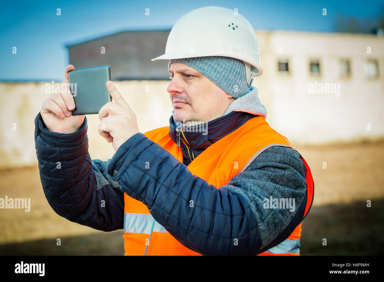 Engineer filmed with tablet PC near building - Stock Image