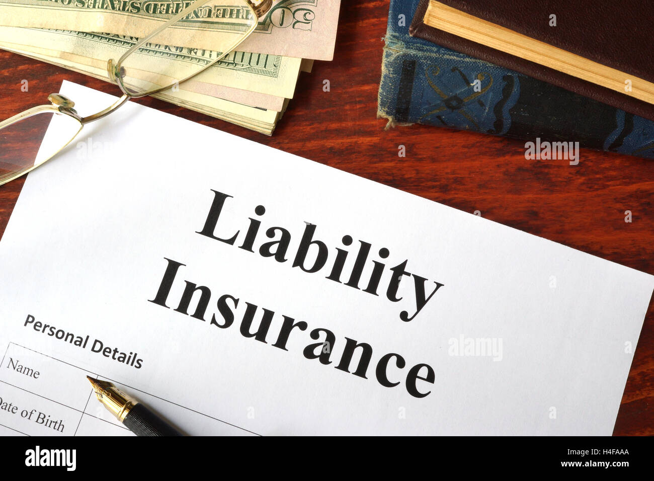 Liability insurance on a wooden table with glasses. - Stock Image