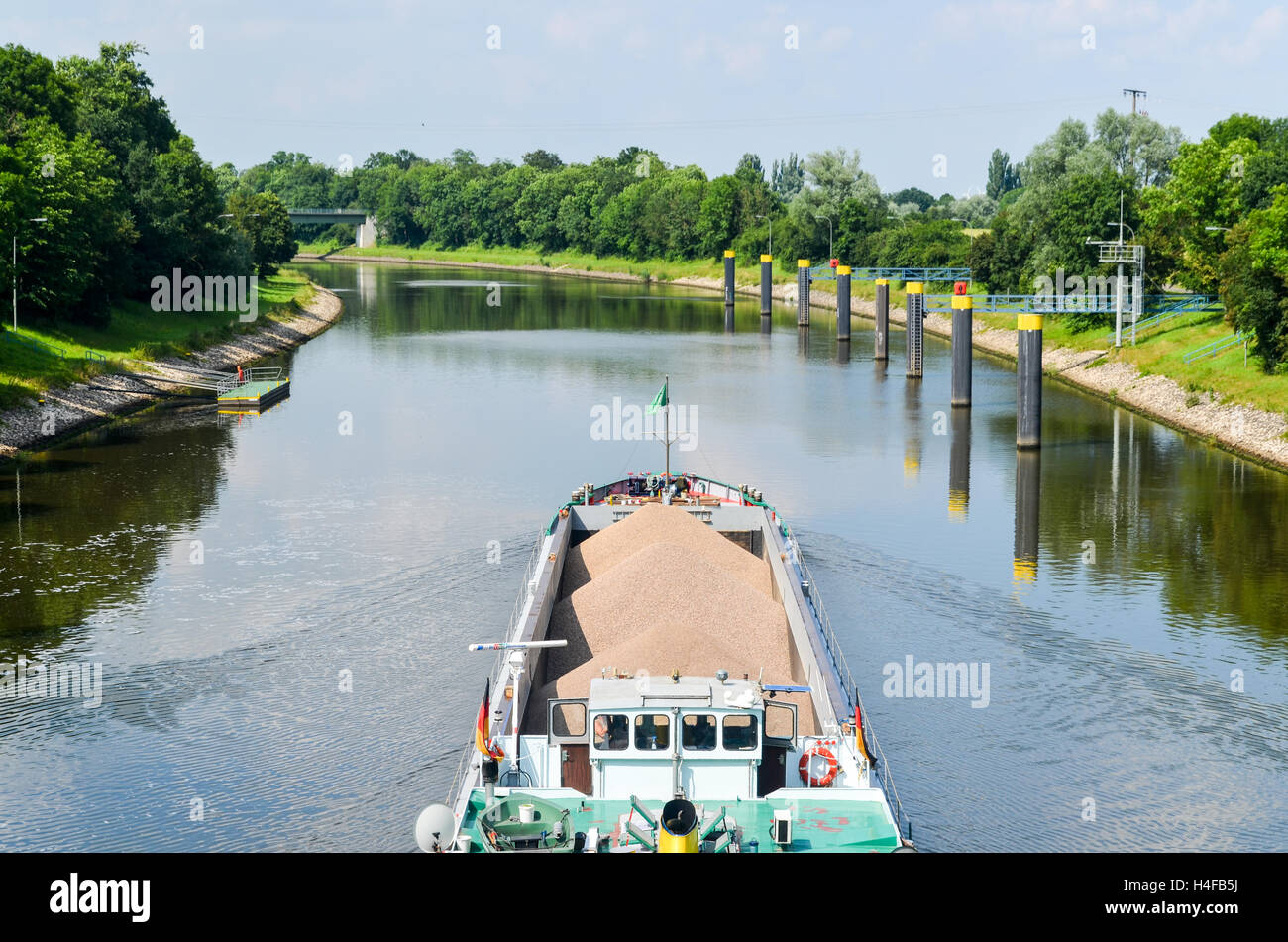 Barge passing a lock on a canal of the Weser river in Germany - Stock Image