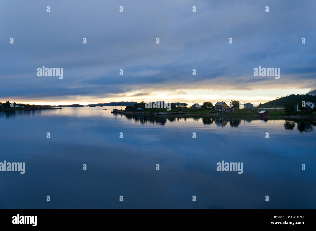 Cloudy sunset at midnight over a few houses on the island of Senja, Northern Norway - Stock Image