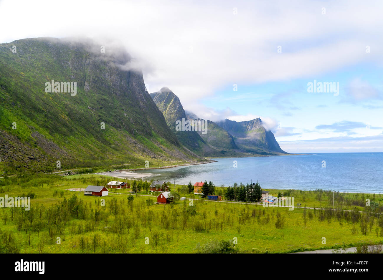 Clouds taking on the rough landscape of Senja, Norway, near a village - Stock Image