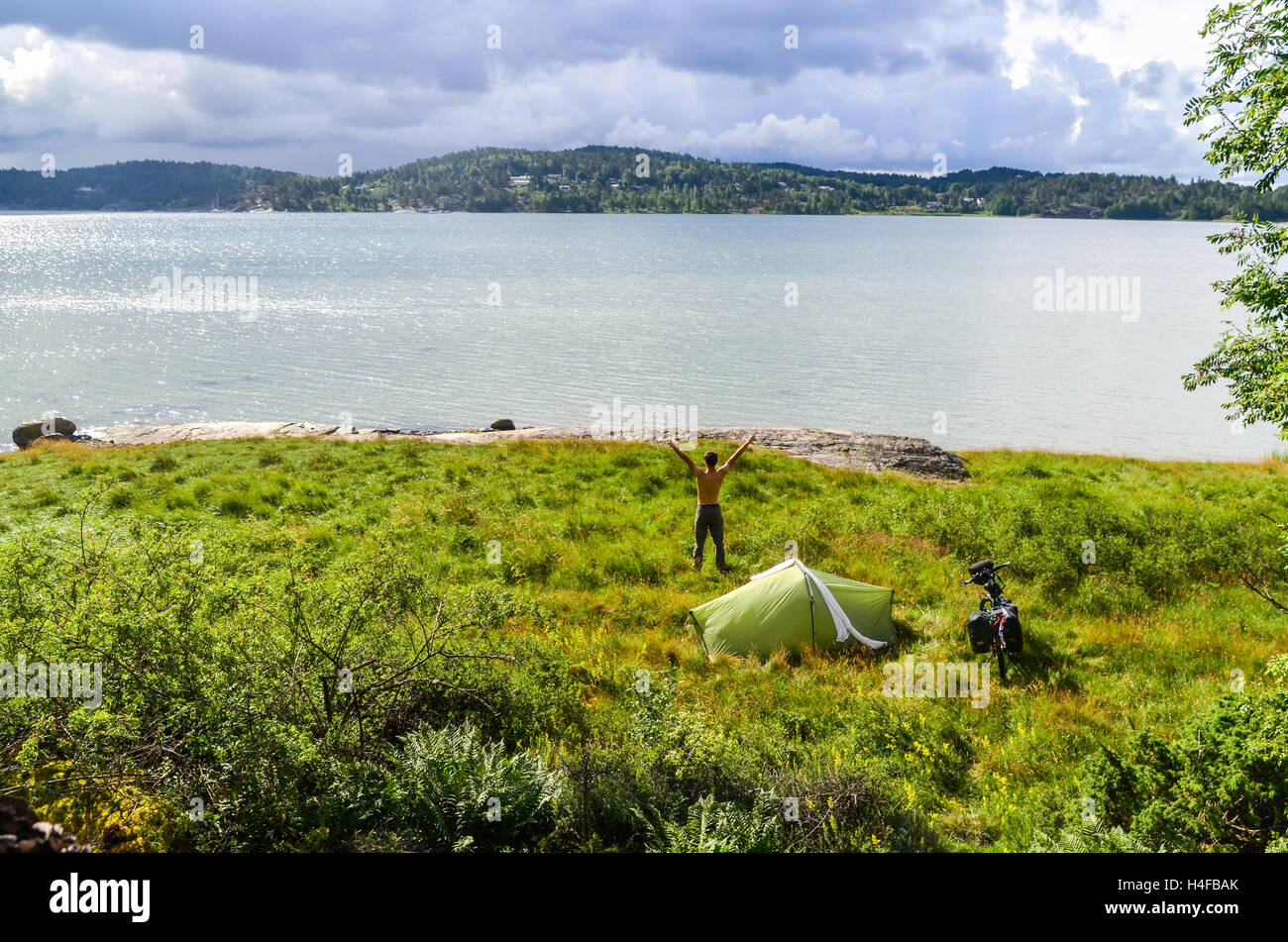 Man standing near tent after camping in Sweden (Orust) - Stock Image