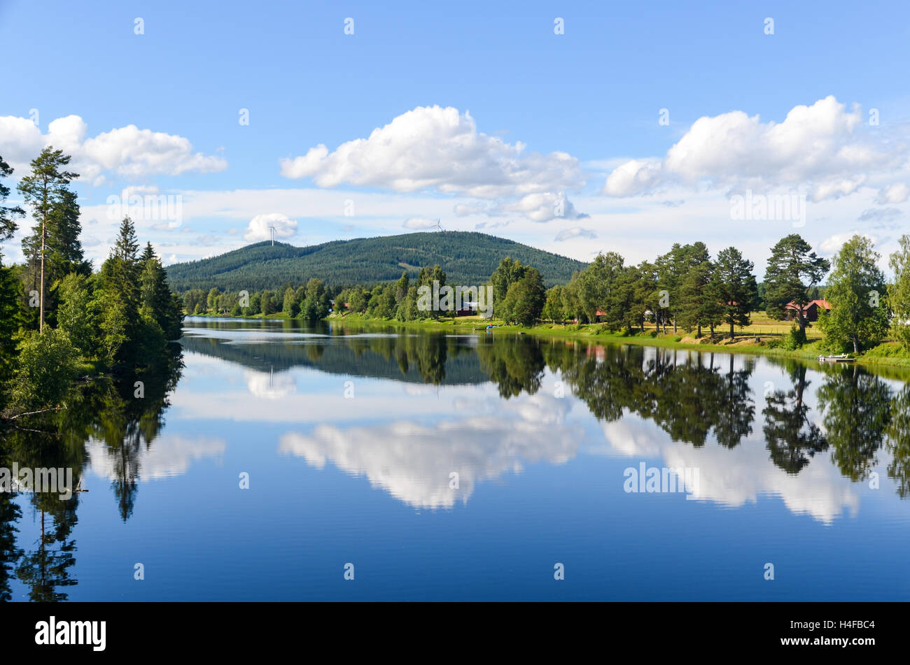 Lakehouse reflecting in the lake in a forest, Sweden Stock Photo