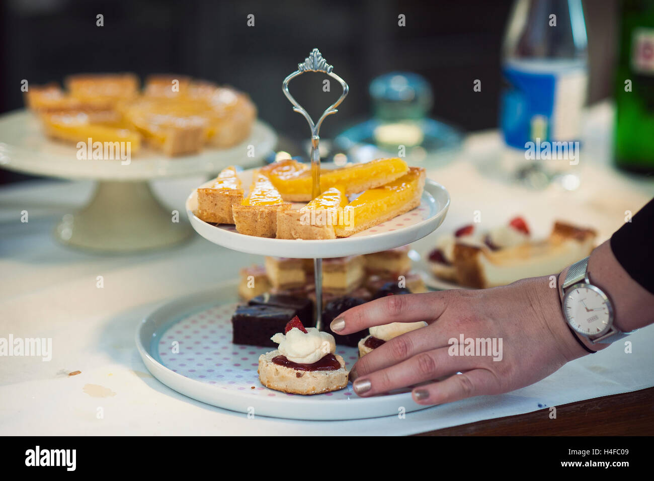 delicious looking cakes on a two tier stand with a person's hand about to take one - Stock Image