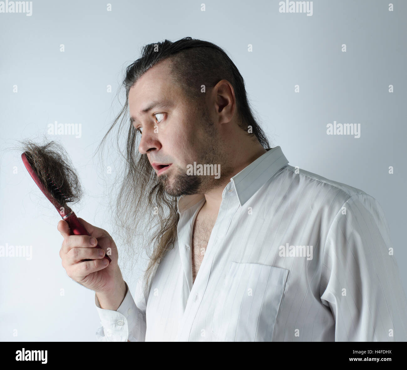 a man looking at a hairbrush with a loosing hair Stock Photo