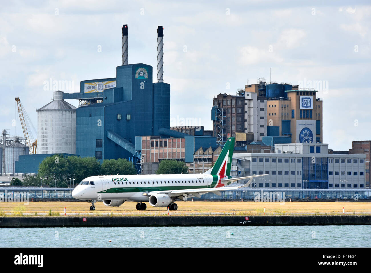 Airplane Alitalia Embraer taxying before take off London City Airport Tate & Lyle Silvertown sugar refinery - Stock Image
