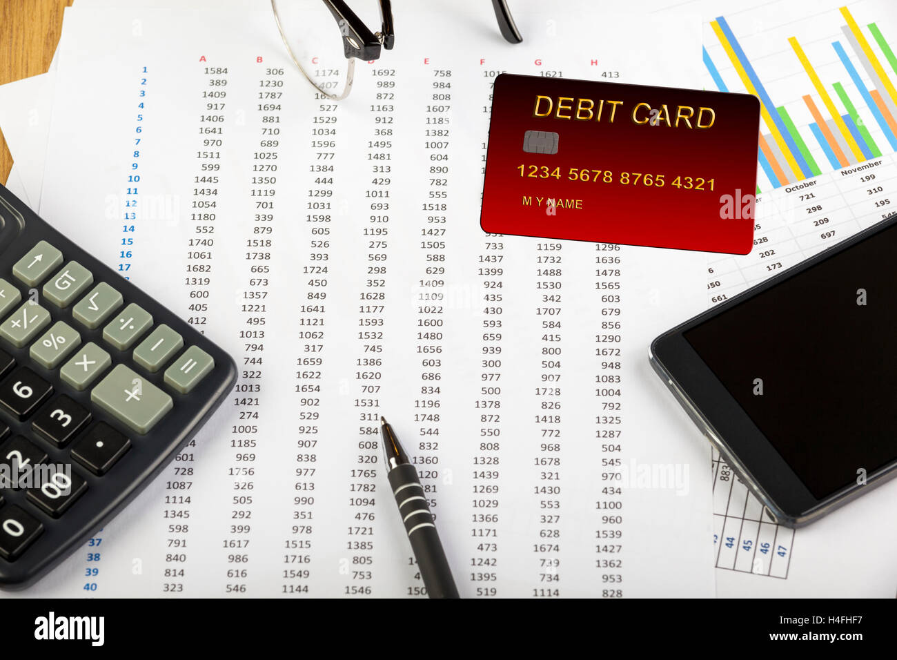 Debit card laying on a spread sheet with a calculator and a smart phone - Stock Image