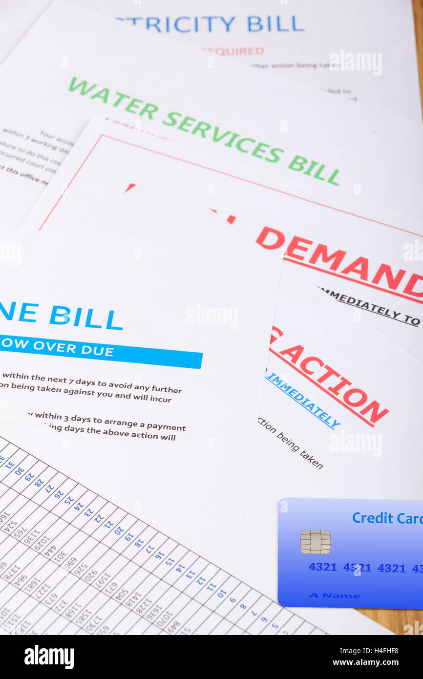 Various bills and demands laying on a table with a credit card - Stock Image