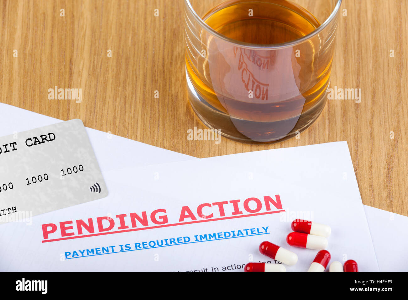 Pending action letter on a table with a credit card and some pills with a glass of whiskey to the side - Stock Image