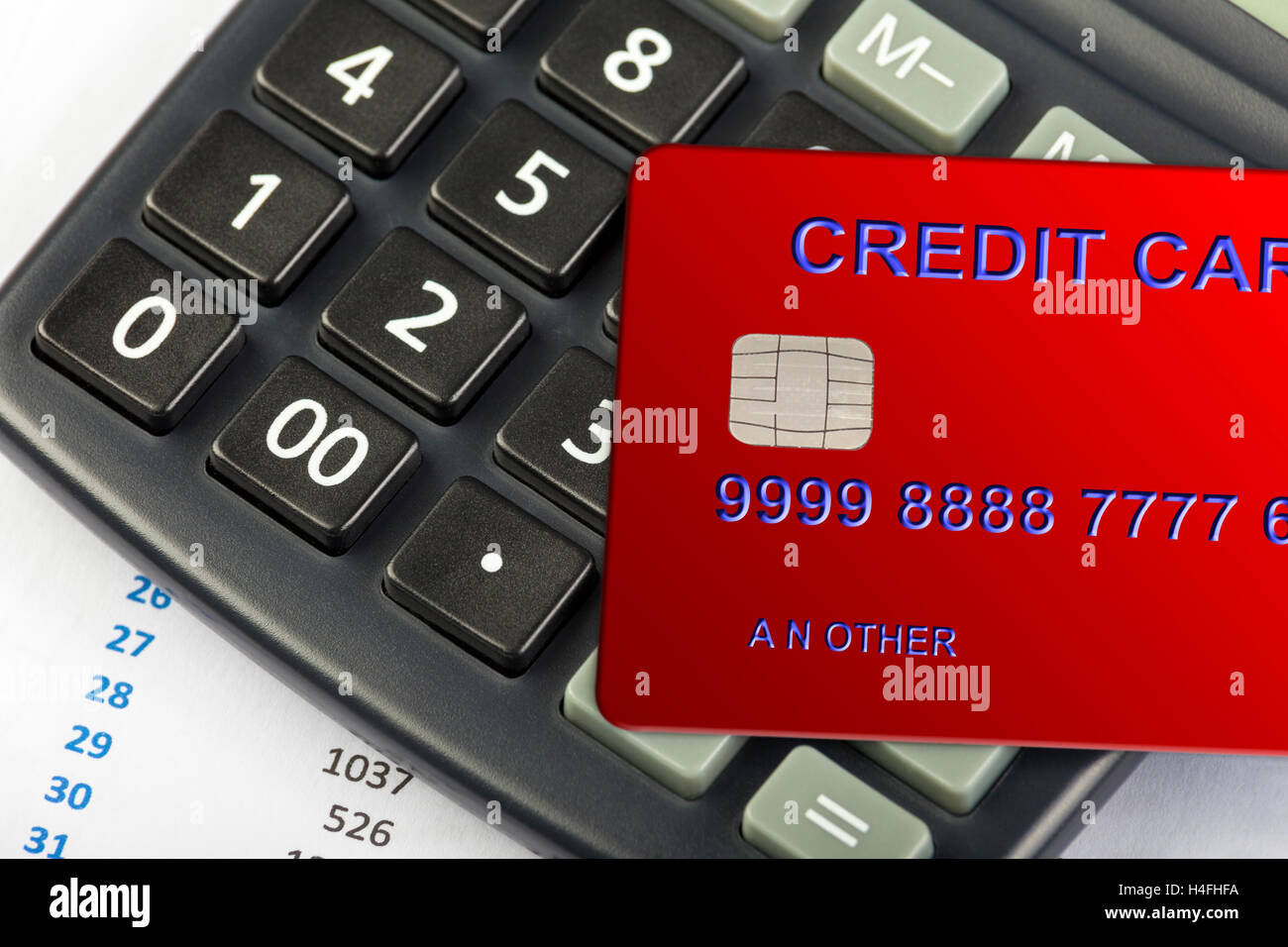 Red credit card laying on a calculator keypad with a spreadsheet on show - Stock Image