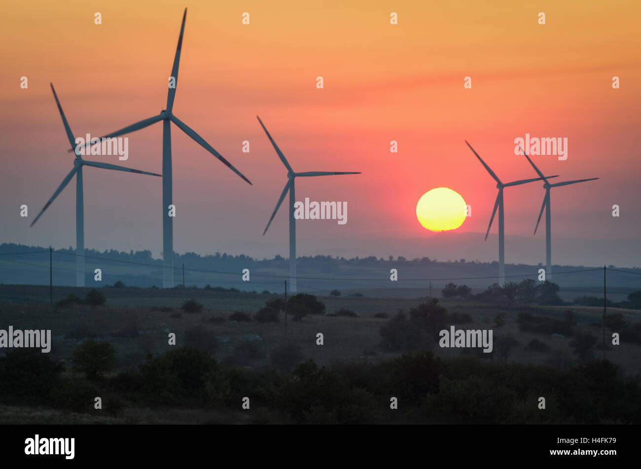 Wind turbines at sunset - Renewable energy concept - Stock Image