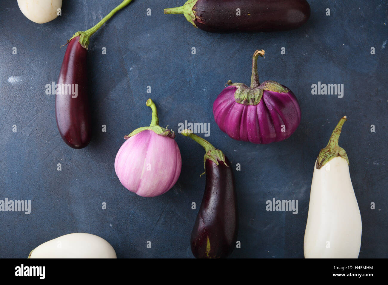 Variety fresh eggplants on slate, food background Stock Photo