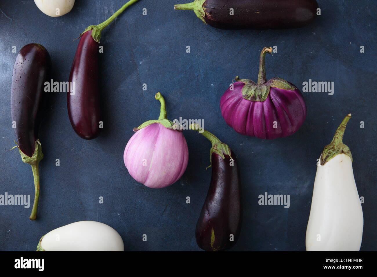 Fresh eggplants on slate, food top view - Stock Image