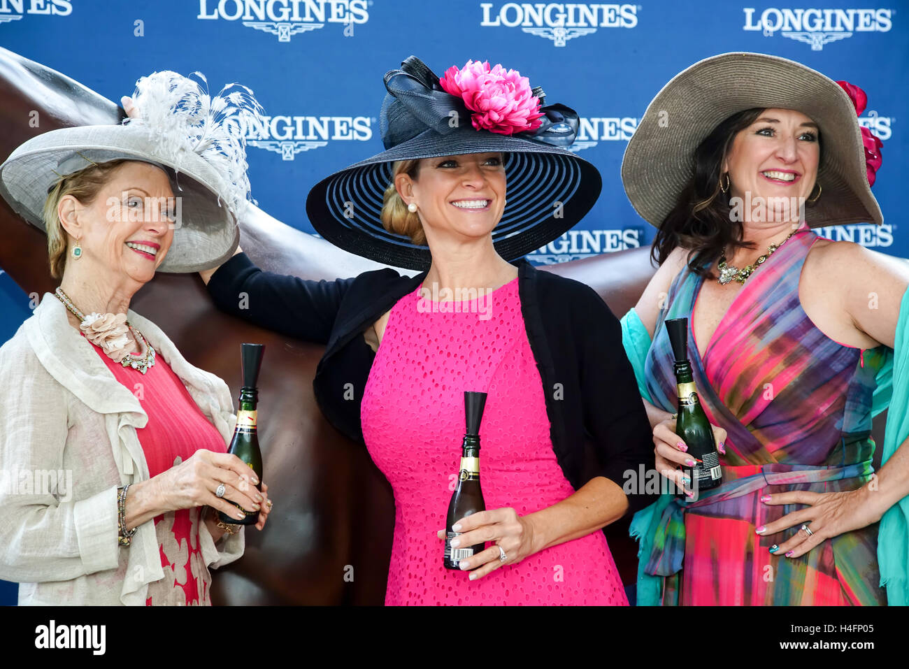 Ladies posing with mini champaign bottles in their Derby Hats at the thoroughbred posing stand. - Stock Image