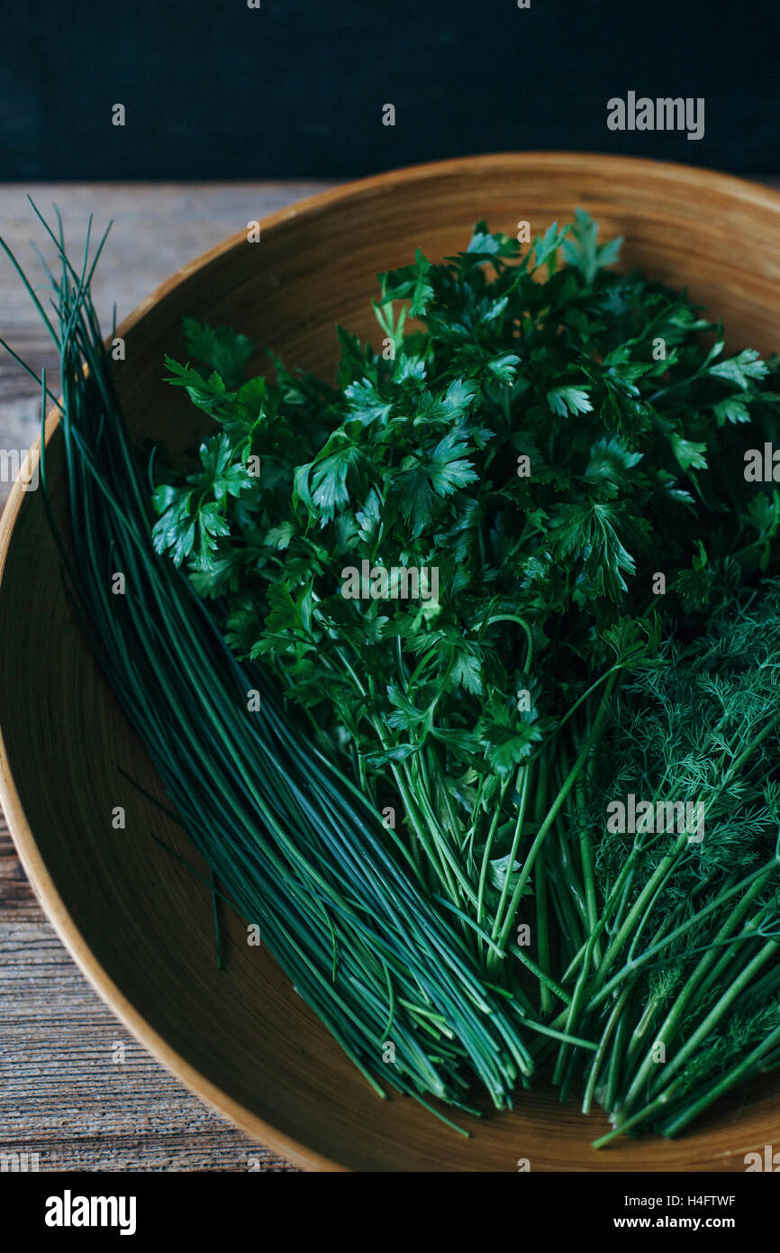 Parsley, chives and dill in a wooden bowl - Stock Image